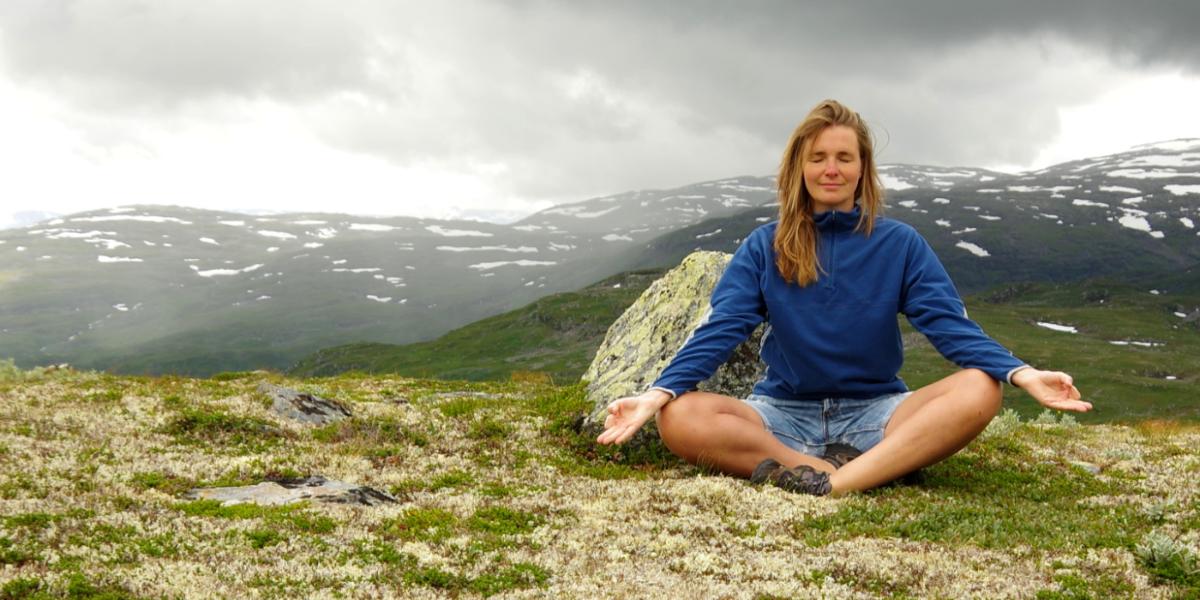 Denise in der Meditation im Hintergrund Berge